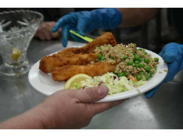A plateful of heaven is prepared for one of the 1,000 diners during a recent Friday night fish fry at St. Clare's in Canyon Country.