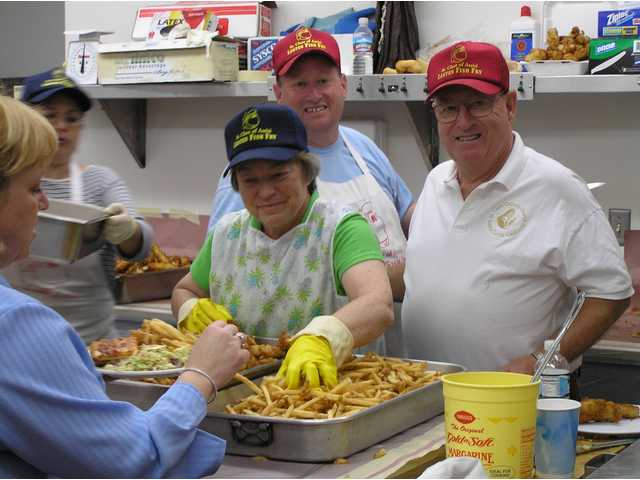 Paul Travers, right, and his son Pat, center, oversee the preparation of more than 1,000 fish dinners at St. Clare's in Canyon Country each Friday night during Lent. They are helped by volunteers (from left) Gina Schlehner, Patty DeAnda and Paulette Ballock.