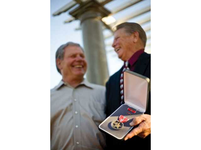 Vietnam war veterans Jim Miller and Bob Good share a laugh Wednesday after Miller was presented with the Bronze Star for valor.