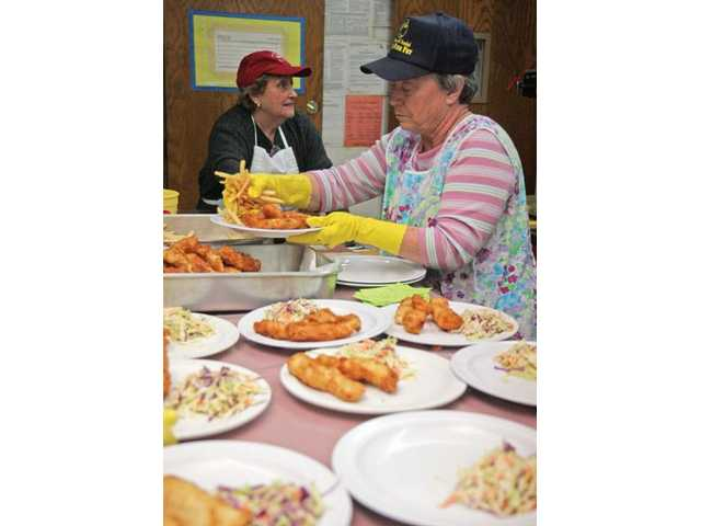 Plates are lined up as volunteer Paulette Ballock adds a handful of french fries to orders during the first Friday of the 32nd annual St. Clare Catholic Church's Lenten Fish Fry event on Feb. 19.