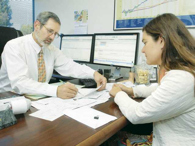 Certified Financial Planner, Michael Green, left, works with client Meghan Walla-Murphy as she get her taxes prepared early in the season Thursday.