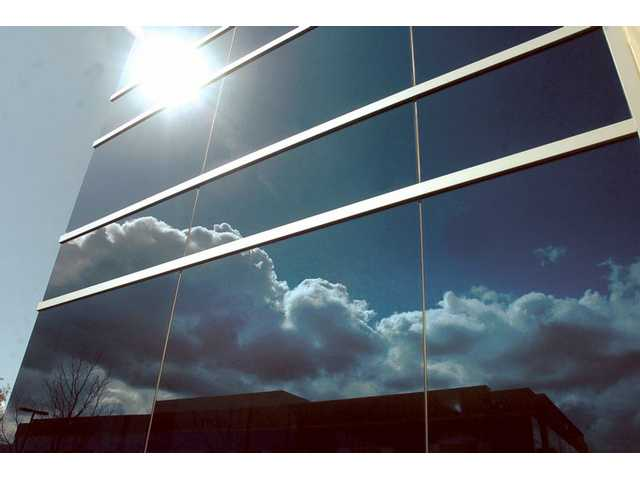 Clouds and sun are visible in the highly reflective windows of the Grubb & Ellis building on Springfield Court. and Valencia Boulevard in Valencia on Saturday.