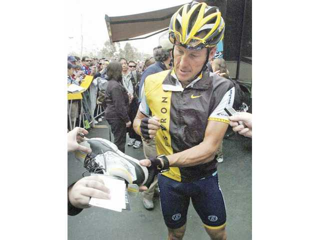 Lance Armstrong signs autographs before the start of the Amgen 2009 Tour of California in the Valencia Town Center parking lot Saturday.