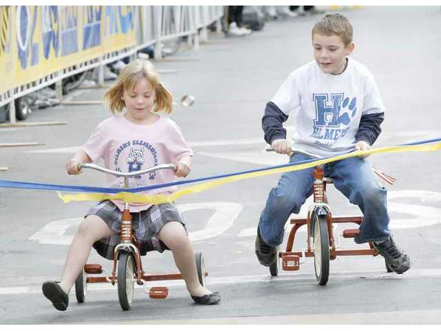 Delaney Scully, 5, left, beats her brother Cole, 8, to the finish line at a tricycle race at the Amgen starting line Saturday.