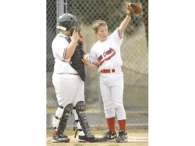 Canyon Country Angels catcher Ricky Cardenez, left, and pitcher Jacob Mertens discuss strategy as they play the Dodgers at Canyon Country's Little League Complex Saturday.