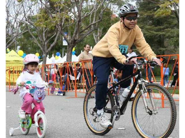 Perry Sun and five-year-old daughter Rebecca of Valencia pedal toward the big Stage 6 finish line on Saturday's Family Ride, one of the Amgen Tour of California cycle race's preliminary activities in Santa Clarita.