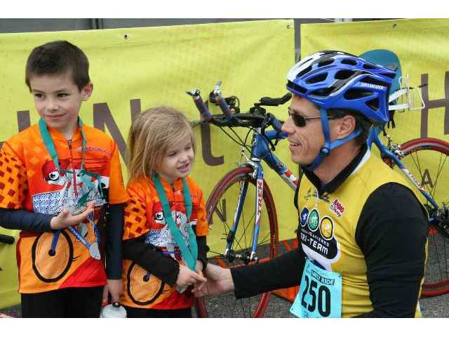 Curt Sandoval, KABC-TV/Los Angeles sports reporter and Valencia resident, congratulates son Trevor, 5, and   daughter Isabela, 5, after they completed the Family Ride Saturday prior to the Amgen cycle race's Stage 6 finish.