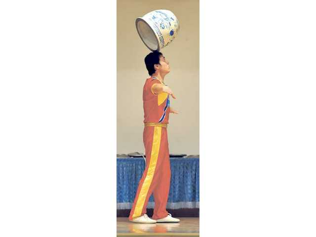 Du Haiyang balances a metal pot on his head.