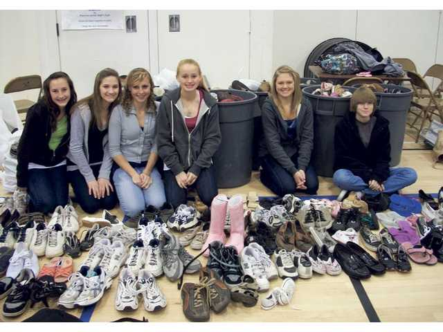 Mitchell Community School students pose with some of the donated shoes.
