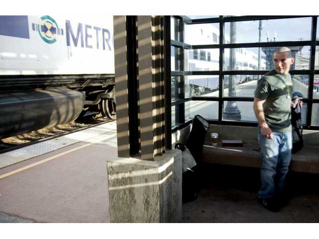 Twenty-seven-year old Vincent Amorosino from Northridge waits for the Metrolink train which will take him back from the Newhall station Monday afternoon. As a student at College of the Canyons, Amorosino commutes via train in order to save money and drive less.