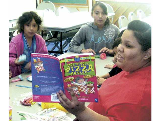 "From left, Kelly Lopez, Emily Chavez and recreation leader Irma Salazar at the Newhall Community Center during the ""Eat Your Words"" program designed for elementary school students."