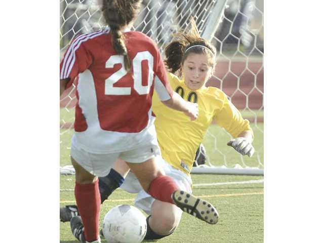 Saugus goalkeeper Bianca Lorenz (00) slides to block the shot of Flintridge Sacred Heart's Breeana Koemans Tuesday at Saugus High School.