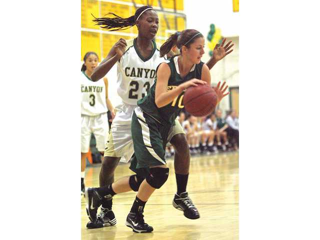Edison's McKenzie Clapp (10) dribbles past Canyon's Alia McCoy (23) at Canyon High on Wednesday in the CIF-SS Division IIAA quarterfinals.