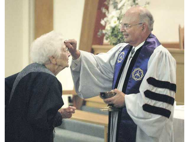 Milada White, left, receives a cross of ash on her forehead from Dr. Stan Fix, pastor of the Friendly Valley Community Church as Ash Wednesday services end Wednesday.