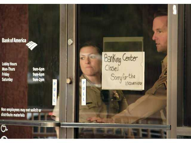 Deputies from the Santa Clarita Valley Sheriff's Station look past a sign indicating the banking center at a Canyon Country branch of Bank of America is closed as they investigate a robbery there Wednesday afternoon.