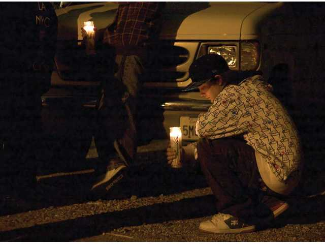A friend of Arias pauses over his candle at the vigil held on Wednesday.