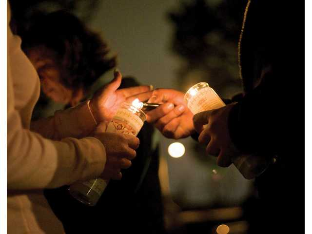 Friends light each other's candles in memory of 18-year-old Jaime Arias, who died in a Sand Canyon Road car crash Monday night. About 45 friends and family members gathered Wednesday night for a candlelight vigil.