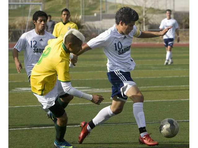 Saugus' Manuel Garza (10) tries to hold off Coachella Valley's Francisco Vazquez (8) during Wednesday's CIF-Southern Section Division III playoff game at Saugus High School.
