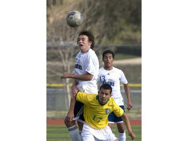 The Centurions' Jacob Sikich leaps over Coachella Valley's Daniel Barragan (17) as Saugus' Manny Padron (13) looks on.