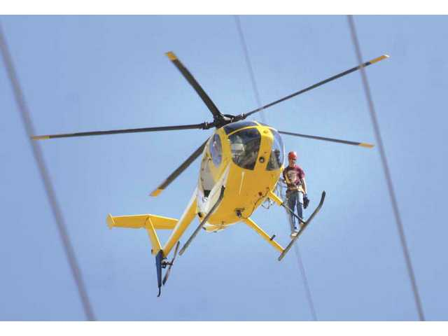 A helicopter carries a lineman to the job site at Haskell Canyon Road Thursday. Southern California Edison contractors are using helicopters to erect new power lines over the northeastern edge of the Santa Clarita Valley.