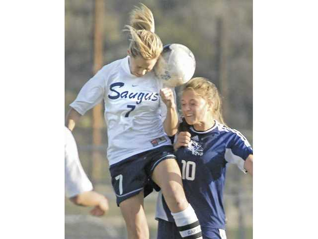 Saugus' Erin Ortega (7) heads the soccer ball as Crescenta Valley's Brittany Berger battles for it Thursday at Saugus High in the CIF-SS Division II quarterfinals.