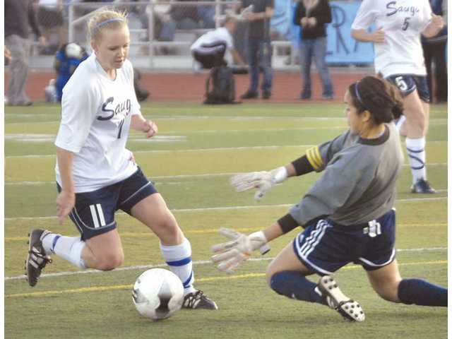 Saugus' Jamie Molacek (11) charges the goal Thursday as Crescenta Valley goalkeeper Amanda Johnson tries to block in the second half.