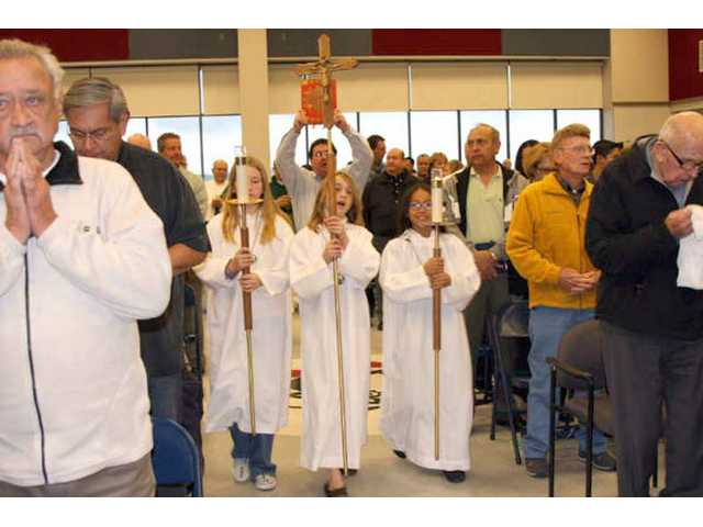 Triplets, left to right, Elizabeth, Michael and Madeleine Togneri, 13, prepare to carry the candles and cross down the altar of Our Lady of Perpetual Help Catholic Church in Newhall for Ash Wednesday service. Ash Wednesday marked the beginning of Lent, a 40-day repentant period during which Catholics and some Christian denominations examine themselves and fast in anticipation of Easter, the religious holiday that marks Jesus' resurrection. Our Lady joined multiple churches around the Santa Clarita Valley that hosted services and Ash Wednesday.