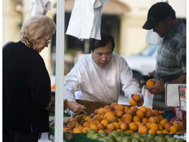 Charles Choi, of Bakersfield, center, arranges his organic fruit as Maria Simione and son Robert Simione, shop for fresh fruit at the downtown Newhall Farmer's Market.