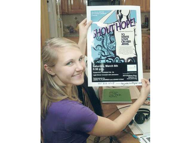 Taylor Bouknight, 17, displays the poster she designed with her sister Shannon for Saturday's Shout Hope benefit concert.