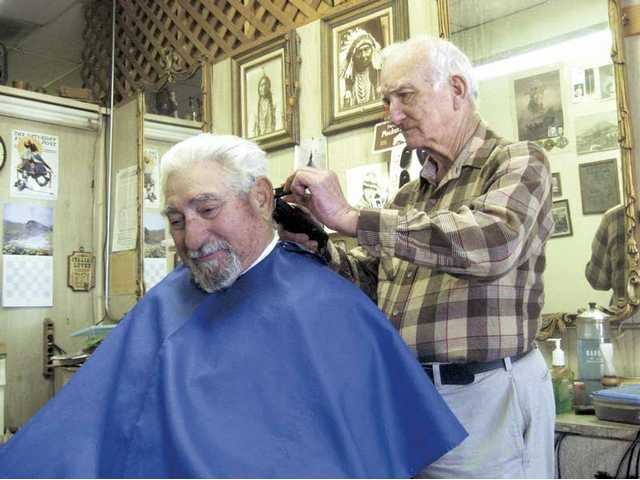 "Jack Lee, of Canyon Country, trims Arnold Torres' hair at Jack's barber shop Thursday. Lee, 74, attended barber college out of high school and has only missed two days of work in his barber shop career. His loyal customers appreciate the ""old-fashioned"" feel of the shop."