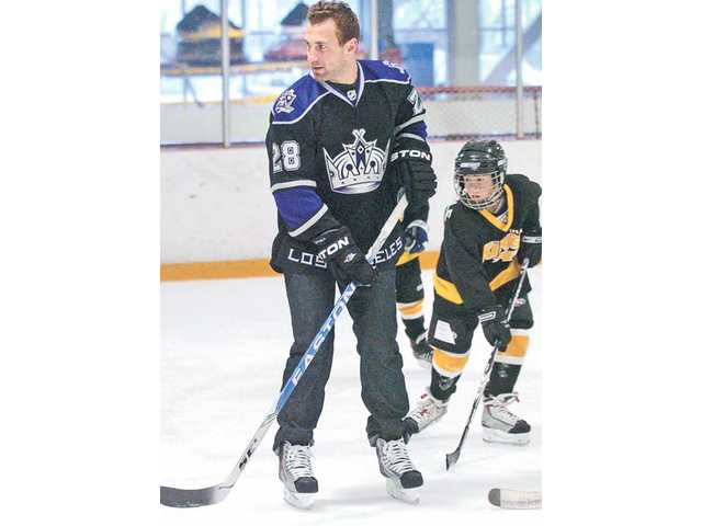 L.A. Kings forward Jarret Stoll works with children during a hockey clinic held at Ice Station Valencia on Saturday.