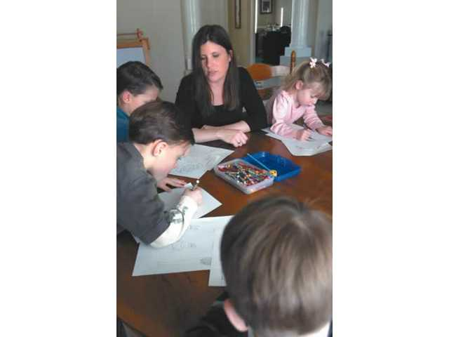 Tricia Schroeder helps her two sets of twins finish their homework at their Acton home. She advises couples who may be expecting multiples to plan in advance, but to be open and flexible once the babies are born.