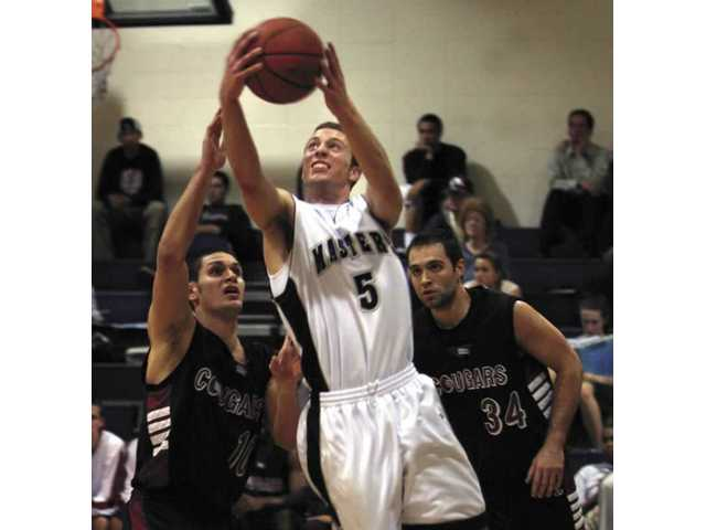 Ryan Zamroz (5) of The Master's College goes for a layup on Tuesday while Azusa Pacific players Mike Danielian, left, and Dave Burgess (34) look on. The Mustangs lost at home and are now 9-9 in conference play.
