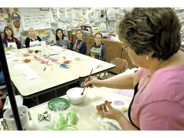 """Nancy Olmos, right, owner of Clarice's Cake and Candy Supplies demonstrates how to paint a thin layer of frosting as she creates a candy box out of cookies at her """"Cookie Madness"""" class held Feb. 10."""