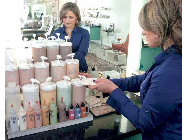 "Jenna Guzman mixes a custom-blended foundation for a client at the ""foundation bar"" at Senna Cosmetics in Valencia."