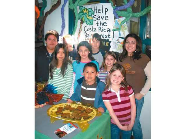 Some of the Boys and Girls Club members from the Newhall branch who volunteered for the Eternal Rainforest Project bake sale and art are, back row Johnny Lopez, Turner Lessard, Taylor Scott and Program Director Rubisela Sanchez. The middle row are Desiree Torres, Alyssa Moreno and Adriana Aguirre. The front row, from left are Joshua Catalan and Alli Ebner. Every $25 they earned will purchase one acre of a rainforest in Costa Rica.
