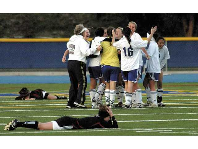 Hart's Kelsey Kraskian, foreground, and Brittiny Reddick, back, lay on the ground after losing to Agoura High in overtime, as the Chargers celebrate. Agoura won at home 2-1 on Friday .