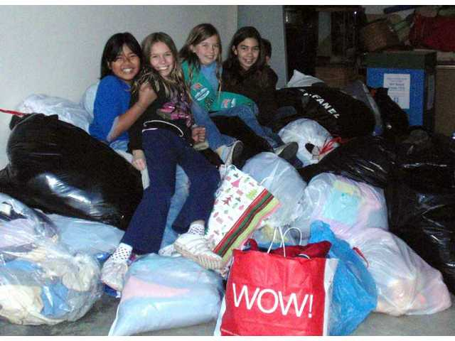 Camille Manzana, Kassi Dobson, Becky Dobson, Victoria Ghio hang out on top of all 627 coats.