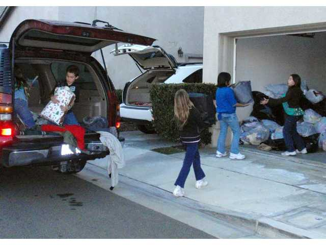 Becky Dobson and Stefano Ghio unload vehicle as Kassi Dobson, Camille Manzana, and Victoria Ghio carry coats to a garage.