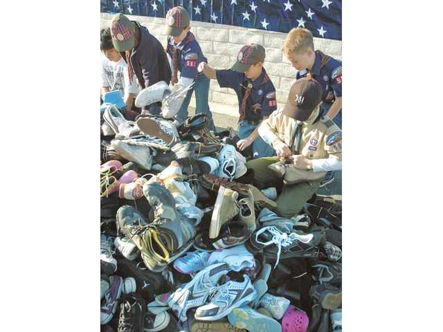 Members of Boy Scout Troop 581 help sort some of the hundreds of shoes collected during the drive.