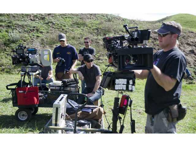 "Camera crew members set up one of three cameras Tuesday in preparation to film a ""napalm drop"" sequence."