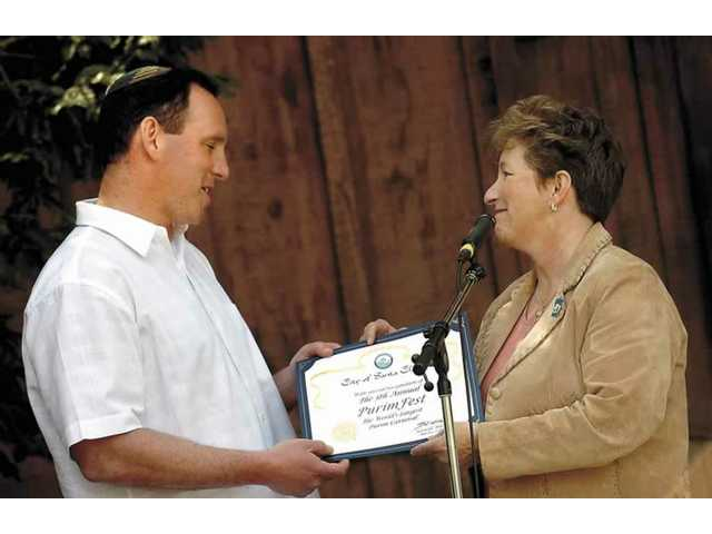 Rabbi Mark Blazer of Temple Beth Ami receives a certificate from Diane Trautman celebrating the fifth PurimFest at Magic Mountain.