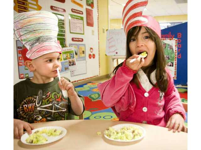 (Left to right) In celebration of Dr. Seuss' birthday, Jason Matwiczak and Kiara Caban enjoy green eggs and ham at La Petite Academy Monday morning. Students spent most of the day reading and doing activities revolving numerous Dr. Seuss books.