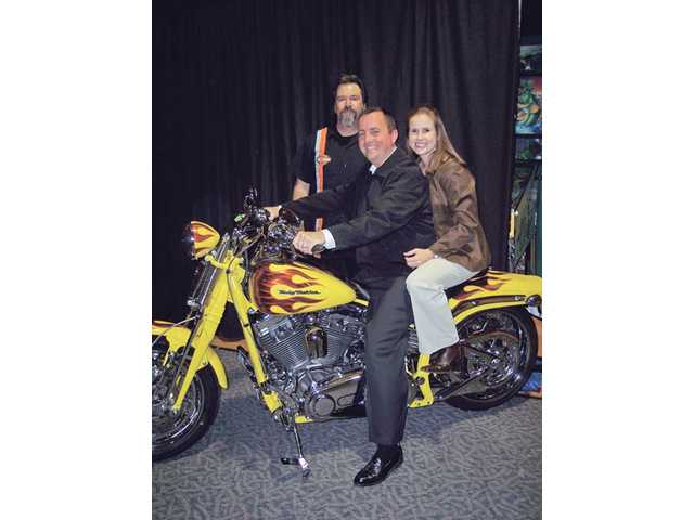 Boys & Girls Club of SCV auction co-chairs Jay and Ashley Thomas sit atop a Harley-Davidson motorcycle as Old Road Harley-Davidson General Manager Doug McGuire looks on.