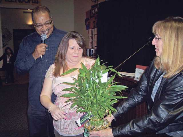Dawn Coupe, center, accepts a plant from Barbara Morris, right and Ventress, for her years of service to the club. She recently resigned.