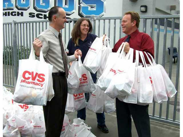 From left to right, CVS manager Eric Harrison, career transition advisor Louise Willard and Saugus High School Principal Bill Bolde in front of Saugus High School after the gift bags were delivered.
