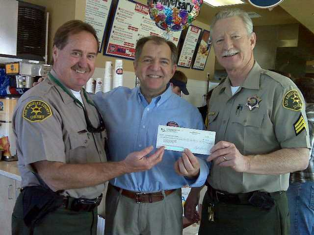 SCV Sheriff's Station Deputy Pat Rissler (left) and Sergeant Gregg Lewison (right) accept a check from Jersey Mike's owner Steve Youlios, who hosted a fundraiser for the station's Explorer program.