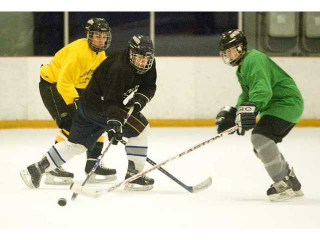 Cougar players  battle for the puck Thursday.