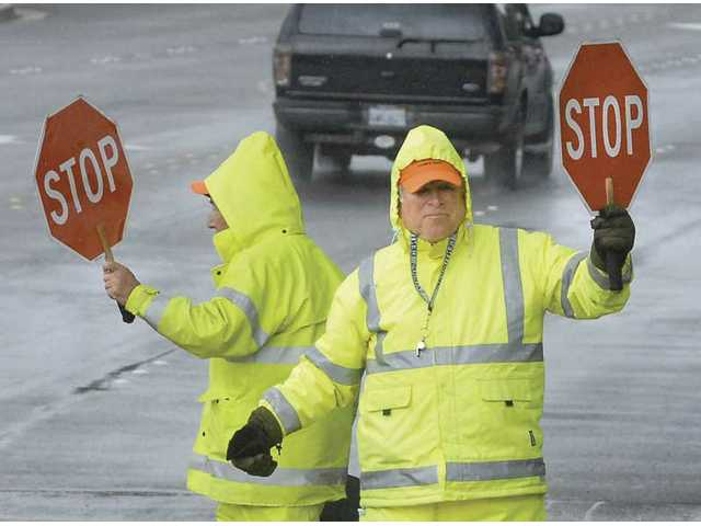 City of Santa Clarita crossing guards Frank Costanzo, left, and Roy Lutes prepare for Santa Clarita Elementary School students to be let out at the corner of Decoro Drive and Seco Canyon Road on a rainy Wednesday afternoon.