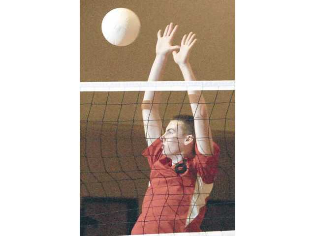 Santa Clarita Christian's Owen Jessup blocks a kill attempt by Cate Wednesday at Santa Clarita Christian School. The Cardinals lost their opener 3-0.